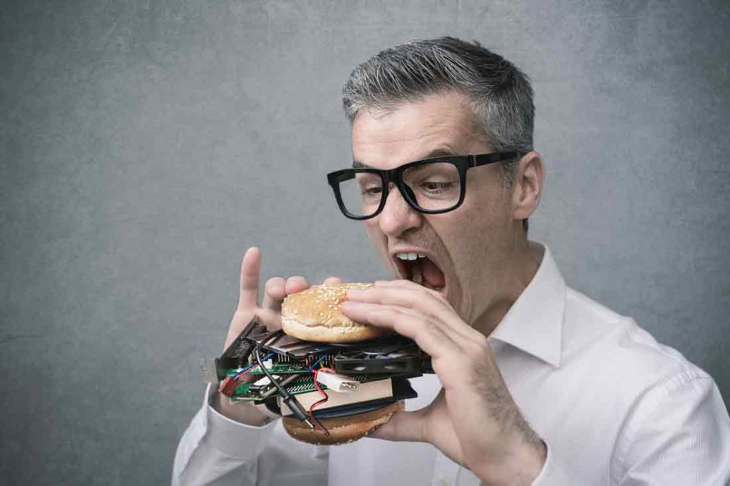 IT office productivity man biting into sandwich with cords